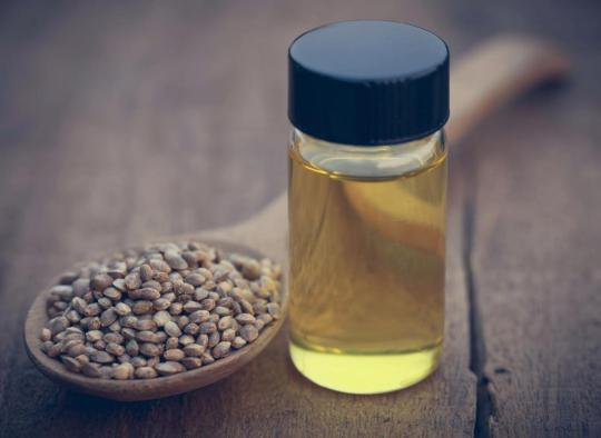 cbd-oil-in-a-bottle-next-to-a-wooden-spoon-filled-with-hemp-seeds